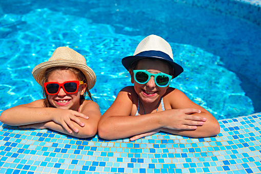 Two cute girls playing in swimming pool. Summer vacation and travel concept