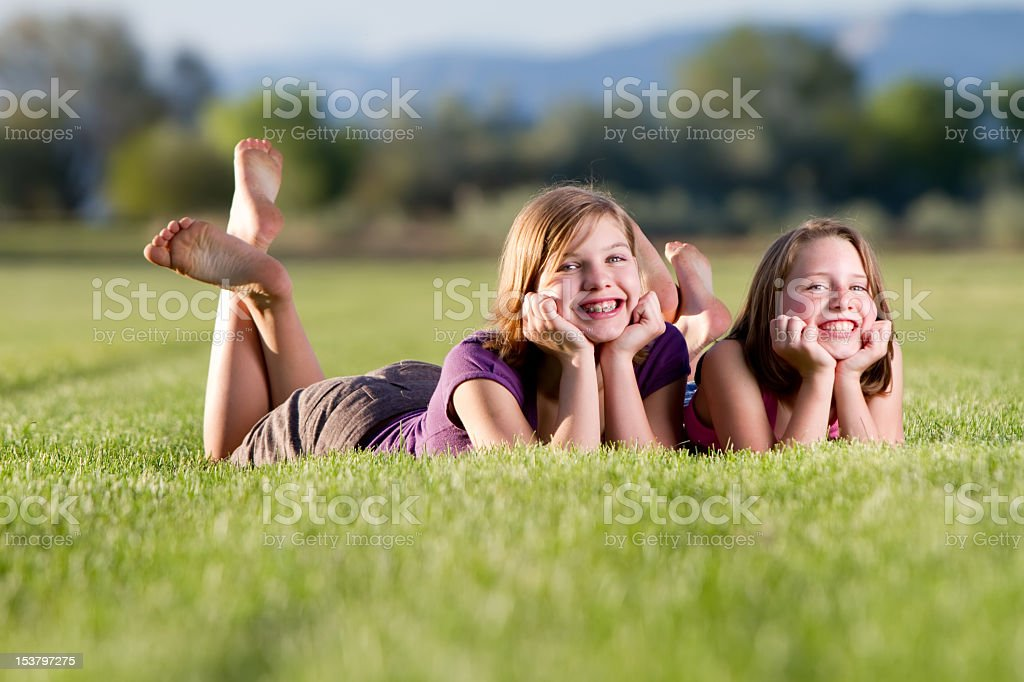 Two cute girls posing in a field stock photo