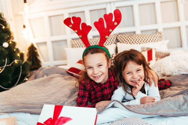 Two cute girls with Christmas presents, playing on the bed stock photo