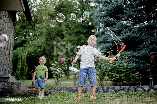 618034312 istock photo Two cute kids blowing bubbles in the front of yard 1166682483