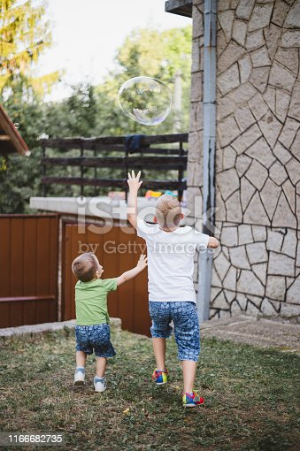 618034312 istock photo Two cute kids blowing bubbles in the front of yard 1166682735