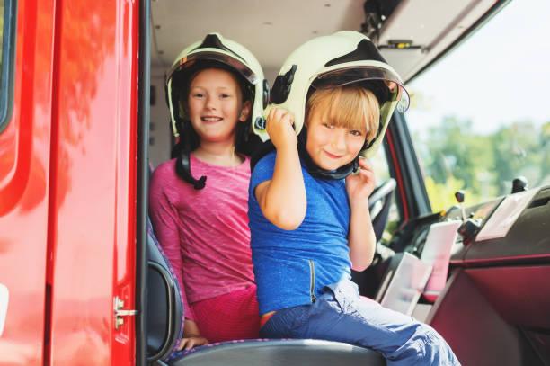 Zwei süße Kinder spielen im Feuerwehrauto, vorgibt, Feuerwehrleute, öffnen Türen-Tag am Feuerwehrhaus. Zukünftigen Beruf für Kinder. Bildungsprogramm für Schüler – Foto