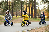 Two cute little boys and adorable blond girl sitting on their balance bikes while moving down asphalt road in natural environment at leisure