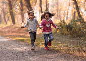 two cute little girls running in a park