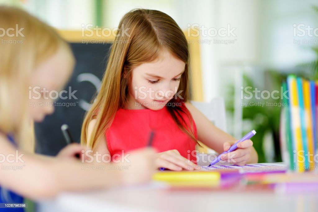 Two cute little sisters drawing with colorful pencils at a daycare. Creative kids painting together. stock photo