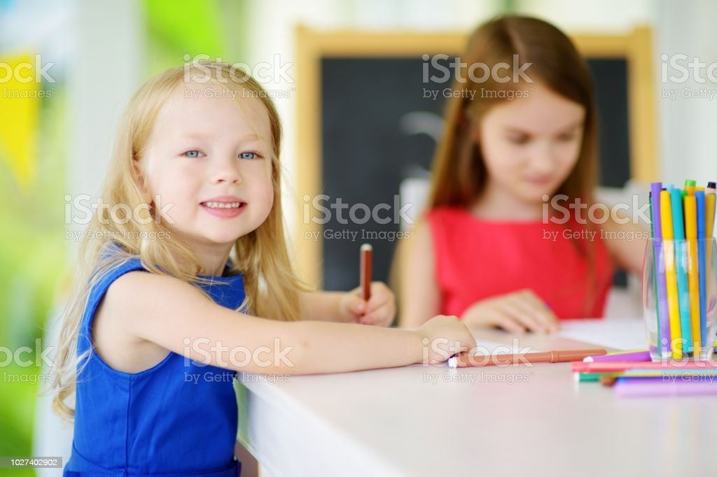 Two cute little sisters drawing with colorful pencils at a daycare stock photo