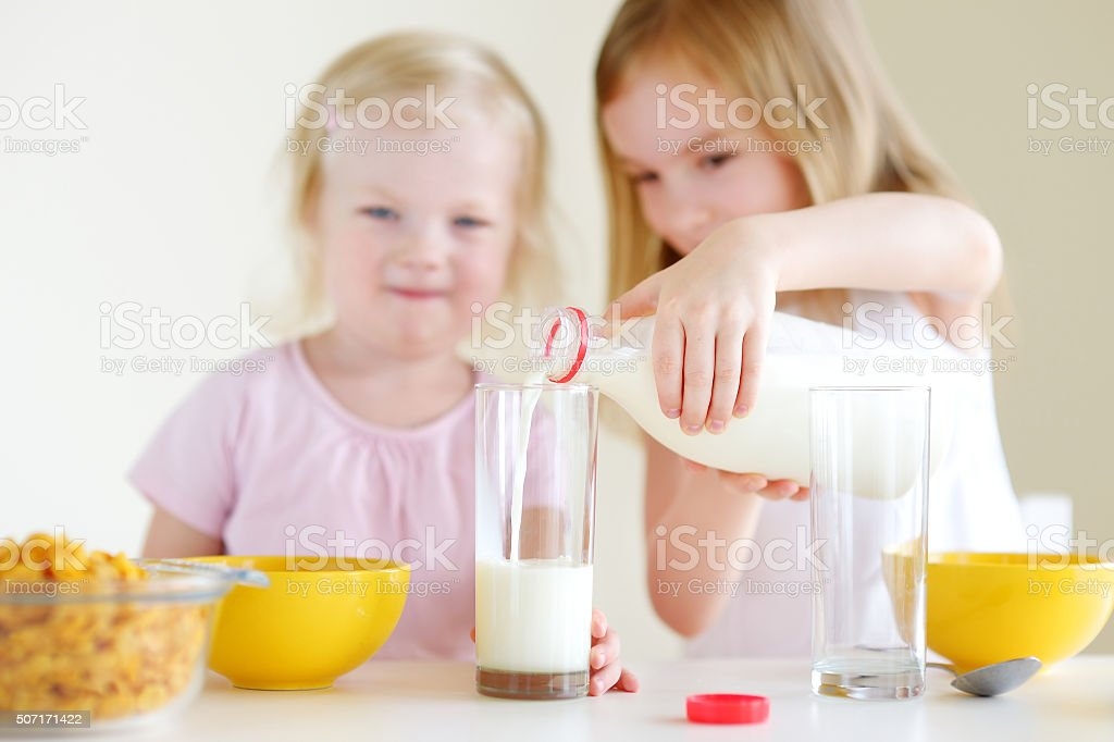 Two cute little sisters eating cereal in a kitchen royalty-free stock photo