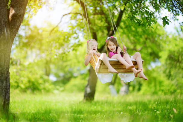 two cute little sisters having fun on a swing together in beautiful summer garden on warm and sunny day outdoors - balouço imagens e fotografias de stock