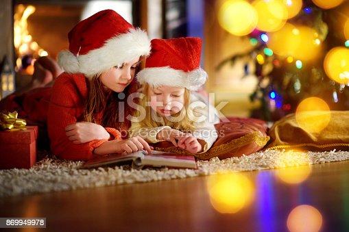istock Two cute little sisters reading a story book together under a Christmas tree 869949978