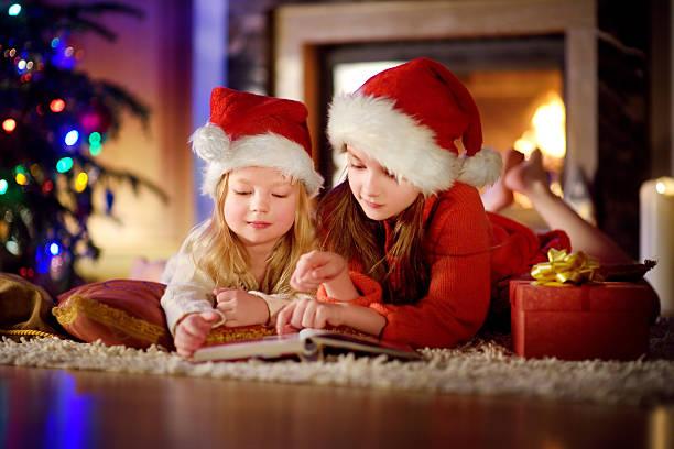 two cute little sisters reading story book under christmas tree - nikolaus geschichte stock-fotos und bilder