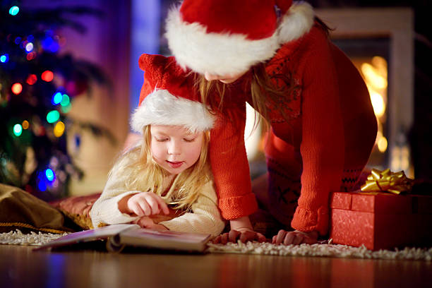 two cute little sisters reading story book under christmas tree - lustige weihnachtsgeschichte stock-fotos und bilder