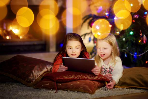 zwei niedliche kleine schwestern mit einem tabletpc durch einen kamin auf weihnachtsabend - kinder weihnachtsfilme stock-fotos und bilder