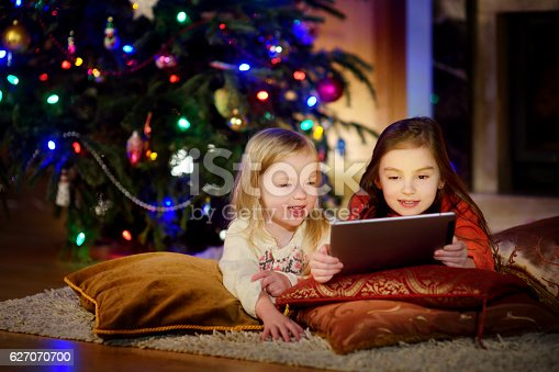 istock Two cute little sisters using tablet by fireplace on Christmas 627070700