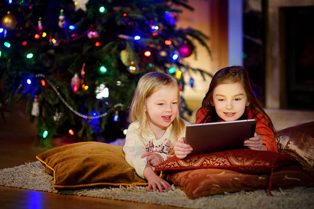 two cute little sisters using tablet by fireplace on christmas - weihnachts video stock-fotos und bilder
