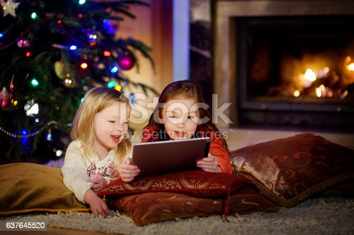 istock Two cute little sisters using tablet by fireplace on Christmas 637645520