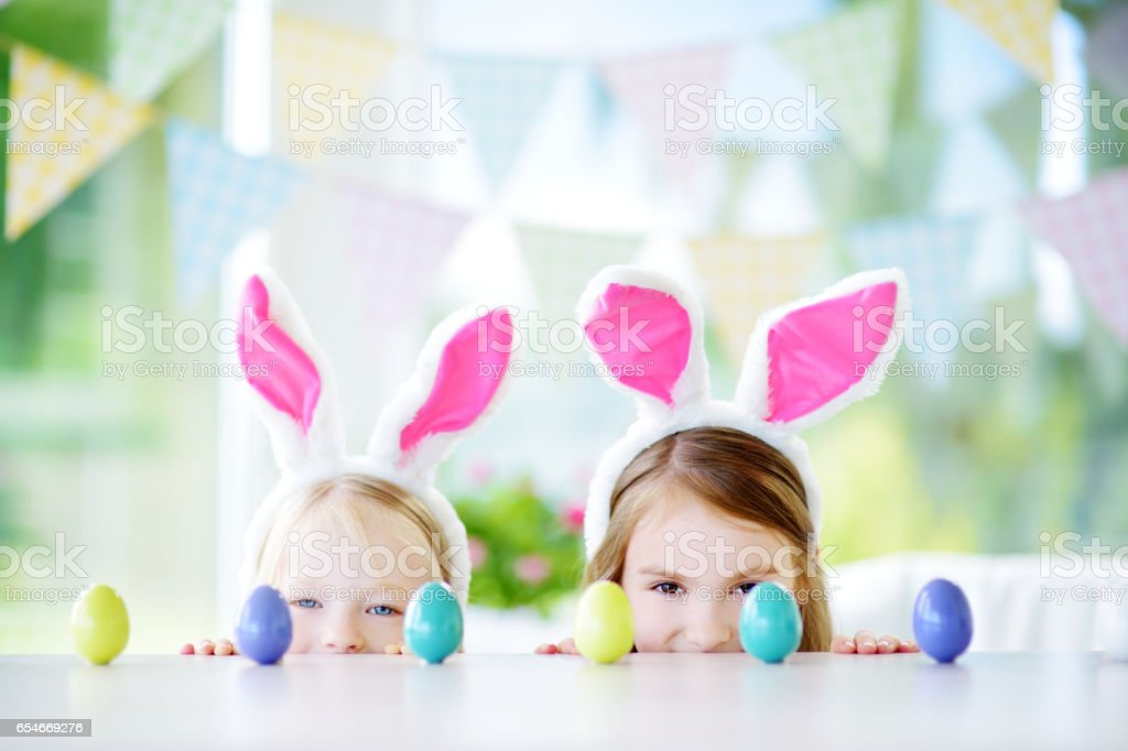 Two cute little sisters wearing bunny ears playing egg hunt on Easter stock photo