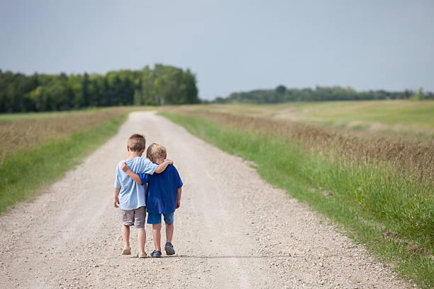 Two Cute Preschool Boys Walking Down the Road