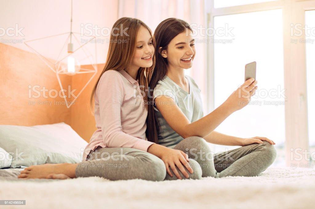 6cbf49f57d5e7 Zwei süße Schwestern unter Selfies auf Bett Lizenzfreies stock-foto