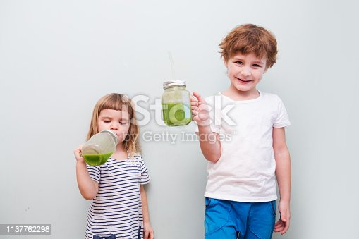 Two Cute smiling kids drinks healthy green smoothie with straw in a jar mug on a gray background