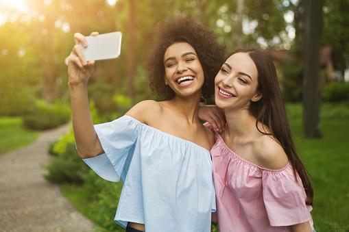 Two cute young women taking selfie in park