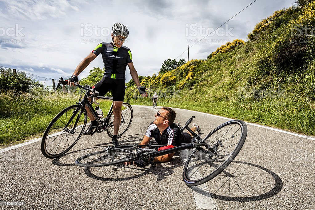 Two Cyclist and Bike Accident in Middle of the Road stock photo