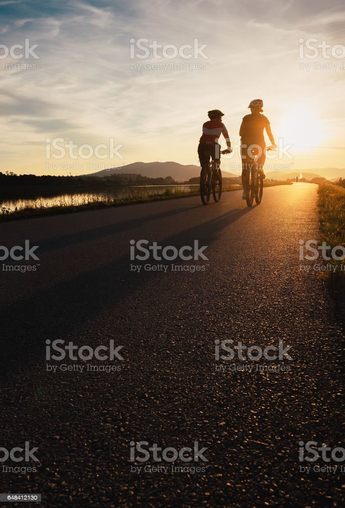 Two cyclists are on sunset road stock photo
