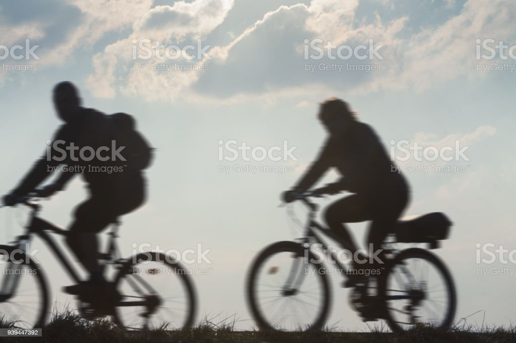 Two cyclists in motion against overcast sky, motion blur stock photo