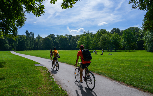 Two cyclists on a asphalt cycling lane in the English garden, a famous park in the centre of Munich, Germany