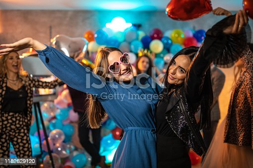 Two beautiful best friends having fun at party , dancing and enjoying together