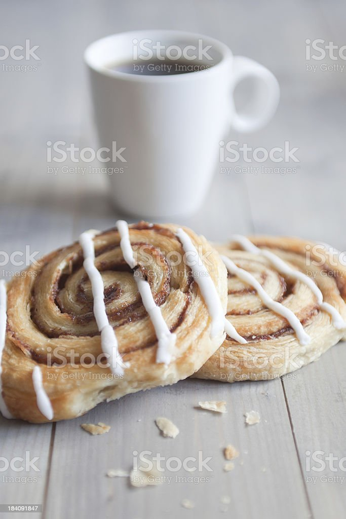 Two Danish Pastries on a wooden table with crumbs by the side. A mug...