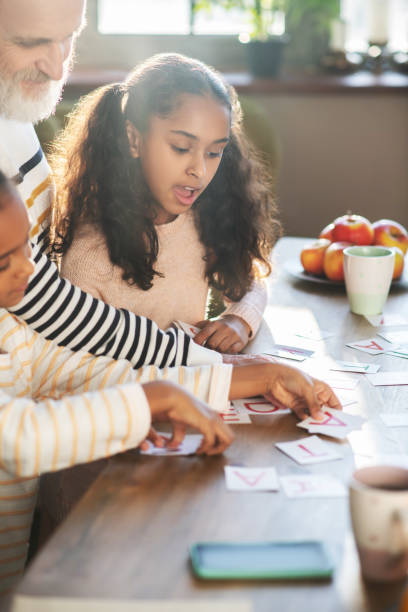 two dark-skinned girls playing words game with their granddad - word game stock pictures, royalty-free photos & images