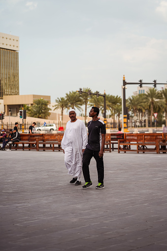 Doha / Qatar - February 18, 2020: two dark-skinned men walking in the vicinity of the Doha Souq Waqif