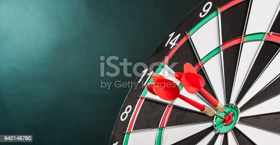 istock Two Darts in the center of the target dartboard 940146760