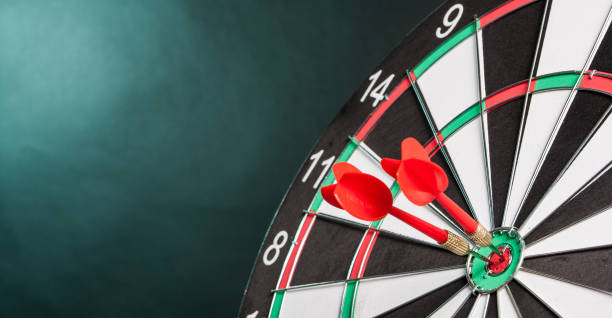 Two Darts in the center of the target dartboard stock photo