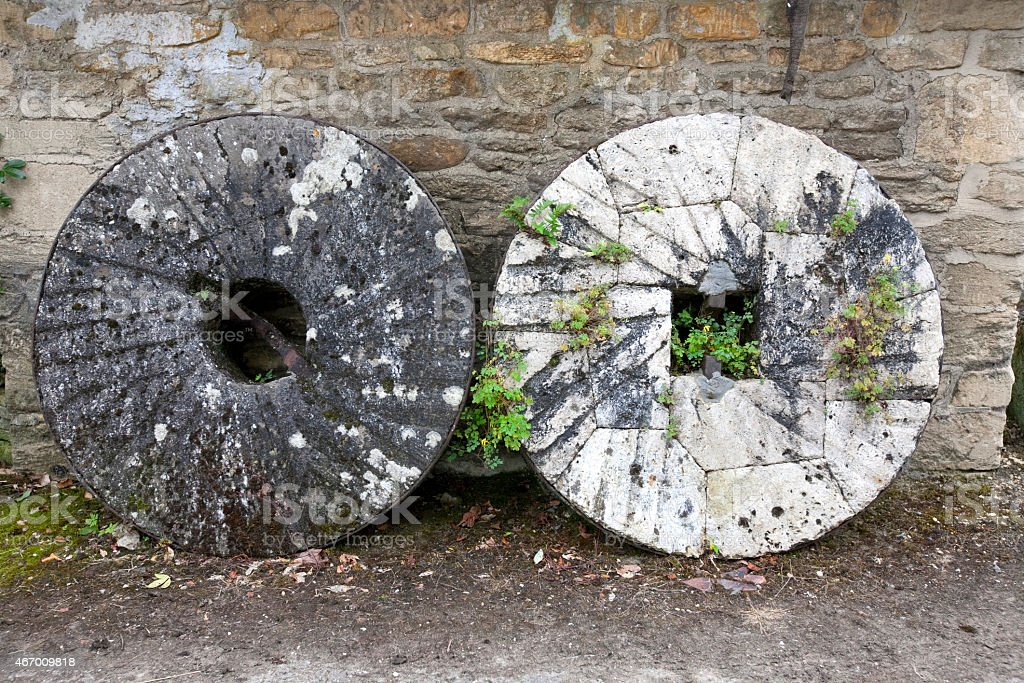 Two decaying large watermill grinding stones stock photo