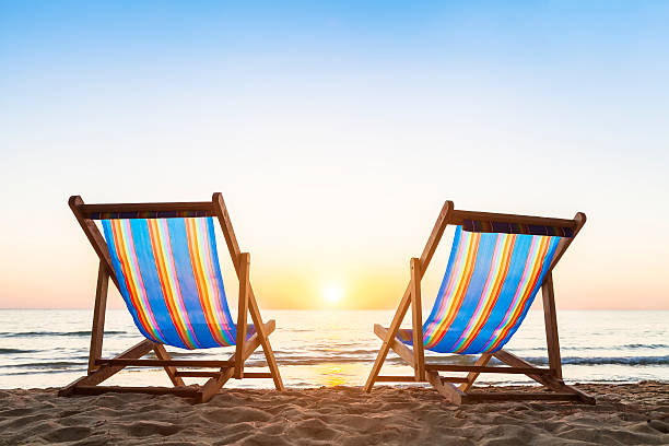 Two deck chairs on a sandy beach at sunset stock photo