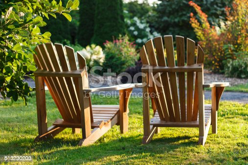 Adirondack chairs overlooking the flowers in the Montreal Botanical Garden at sunset.