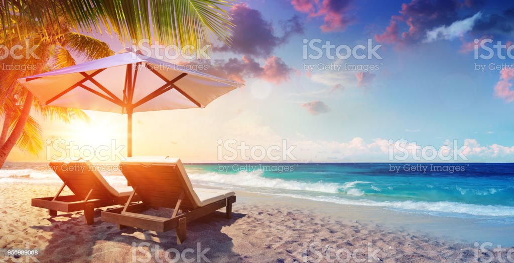 Two Deckchairs Under Parasol In Tropical Beach At Sunset stock photo