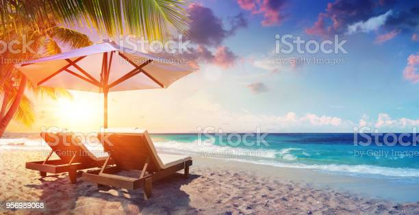 Photo of Two Deckchairs Under Parasol In Tropical Beach At Sunset