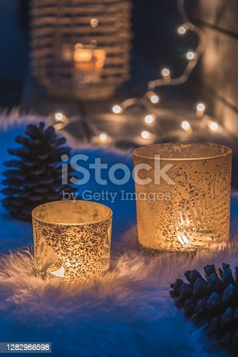 Two decorative glasses with tealights on a lambskin on a veranda in the blue hour, fairy lights and candle light in deh background, cozy atmoshpere, vertical stock photo