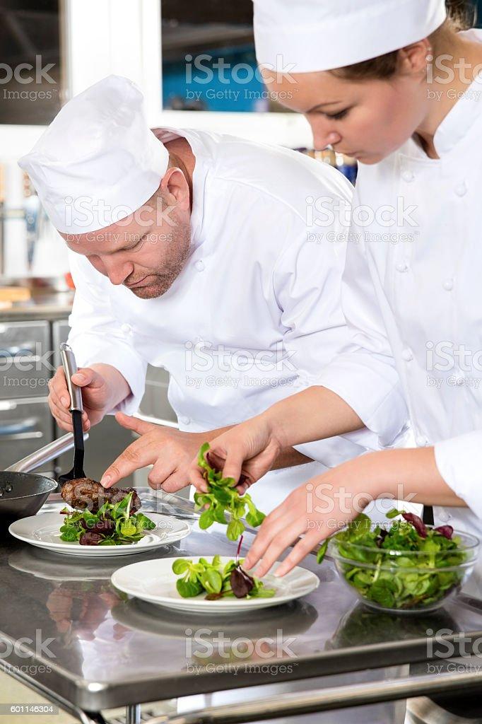 Two dedicated chefs prepares steak dish at gourmet restaurant - Photo