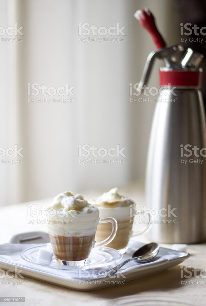 two delicious cup of italian coffee cream on the table near a kitchen...