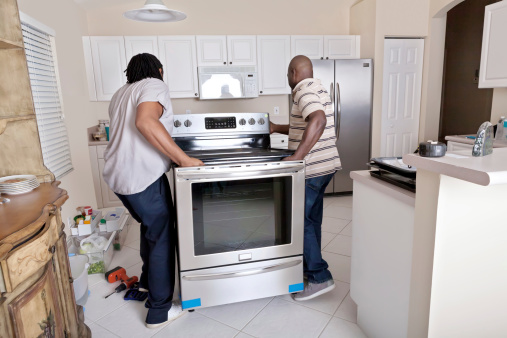 Real Situation- Delivery man taking the plastic protective covering off a new stove