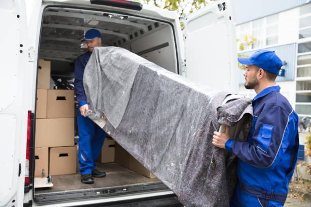 zwei männer entladen möbel aus fahrzeug - umzug transport stock-fotos und bilder