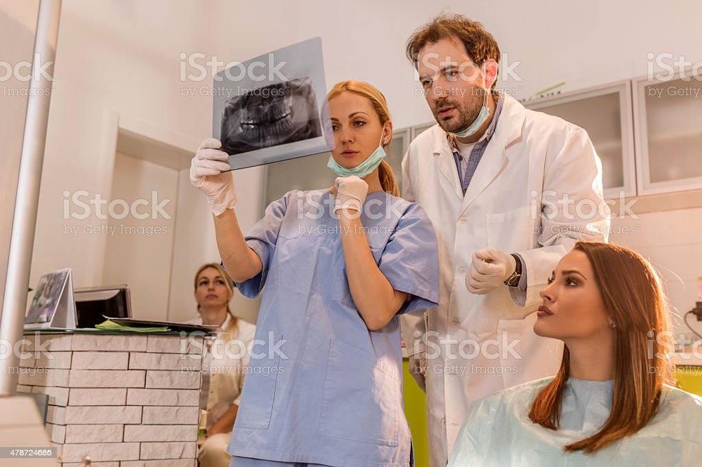 Two dentists looking at Orthopantogram of a young woman. stock photo