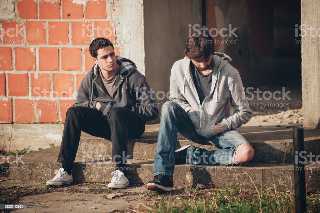 Two depressed and sad young buddies friends thinking about problems stock photo