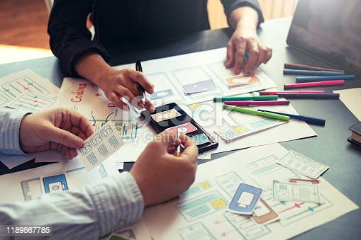 1133505958 istock photo Two designer creativity drawing a website outline and website ux app development on mobile phone. 1189567785