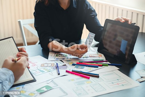 1133505958 istock photo Two designer creativity drawing a website outline and website ux app development on mobile phone. 1189567806