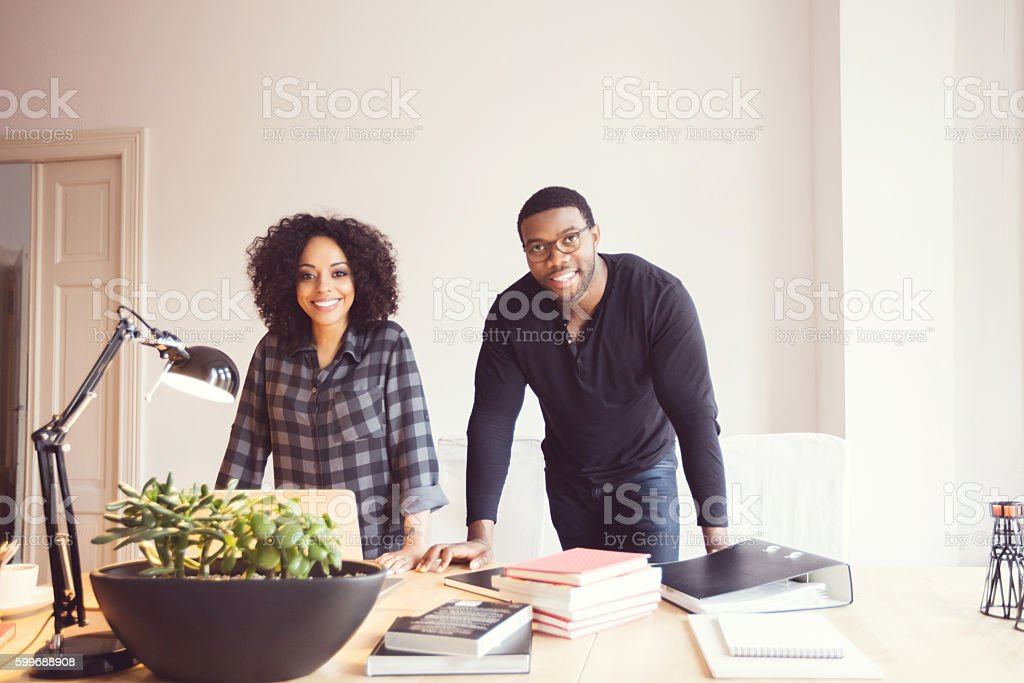 Two designers in the office Afro american young man and woman in the office, smiling at camera.  Adult Stock Photo