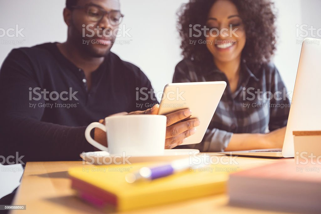 Two designers in the office, using a digital tablet Afro american young man and woman in the office, using a digital tablet together. Adult Stock Photo